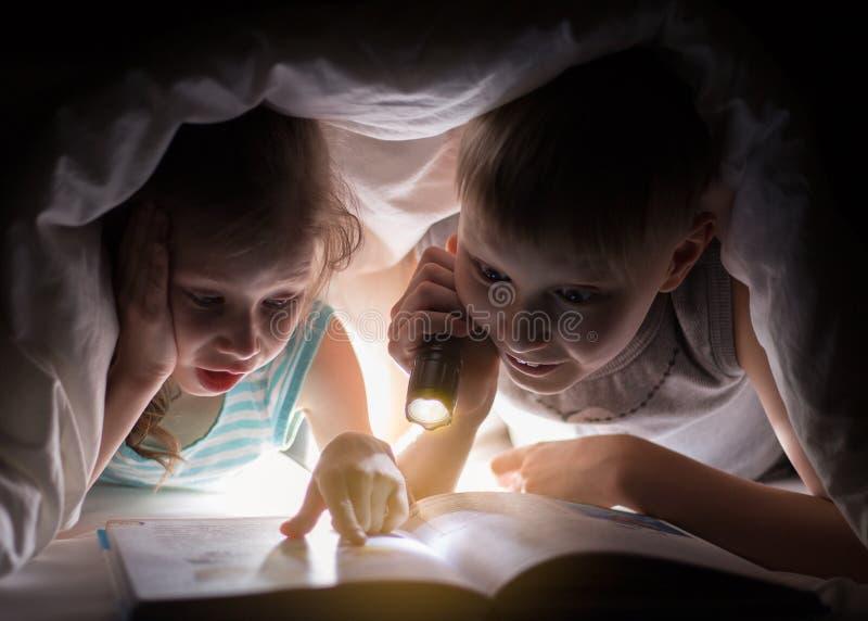 A irmã e o irmão estão lendo um livro sob uma cobertura com lanterna elétrica Menino consideravelmente novo e menina bonita que t imagens de stock