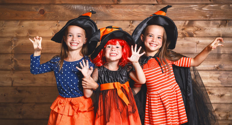 A irmã engraçada das crianças junta a menina no traje da bruxa no Dia das Bruxas fotos de stock