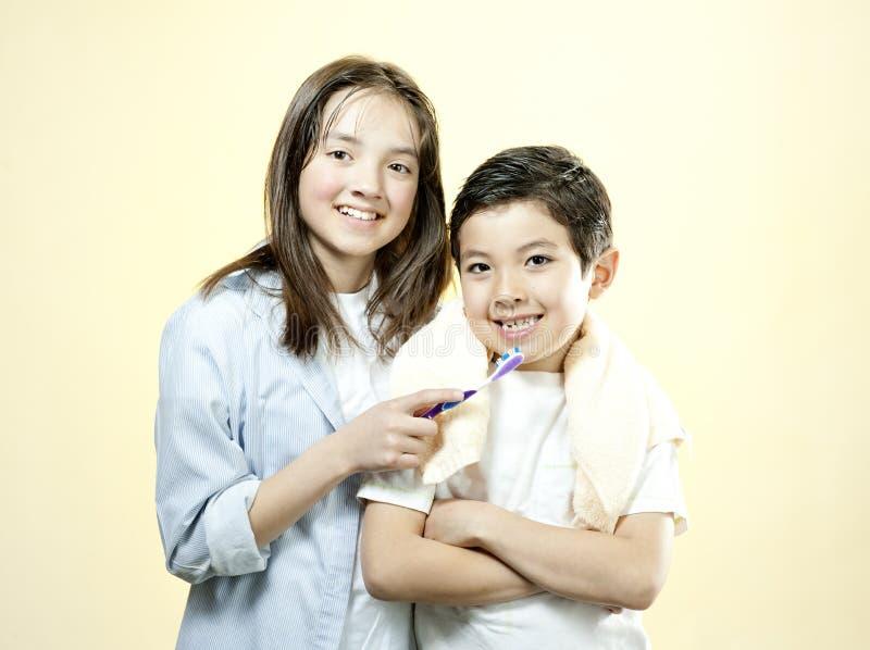 A irmã guarda a escova de dentes para o irmão. imagem de stock royalty free