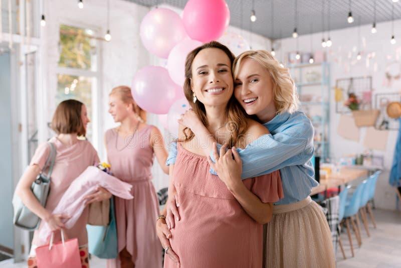 Irmã louro-de cabelo de sorriso que abraça sua menina de antecipação foto de stock