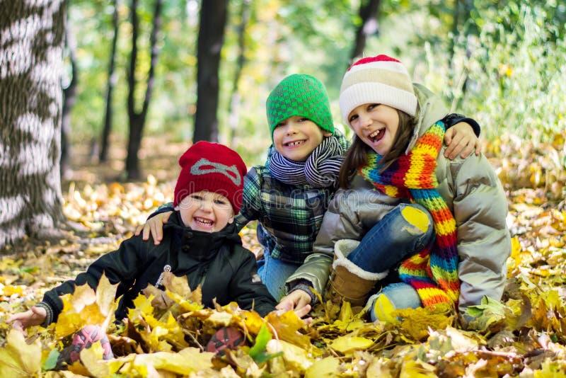 Irmã mais idosa e dois irmãos mais novos nas folhas de outono felizes fotografia de stock