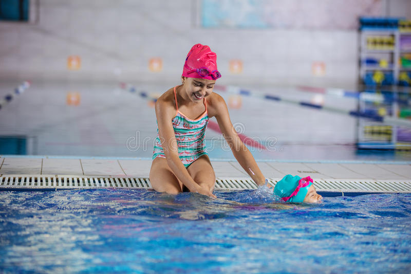Irmã mais idosa que olha o mais novo nadar ao longo do cheiro da associação fotos de stock