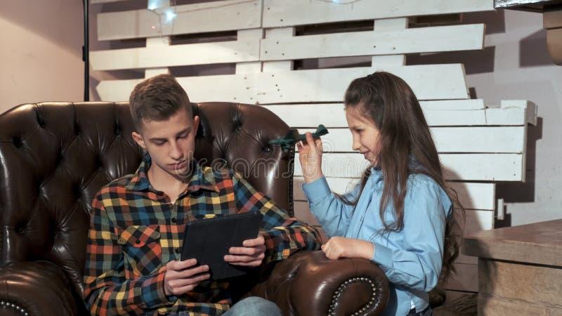 Irmã mais jovem perturbando irmão para surfar na Internet fotos de stock royalty free
