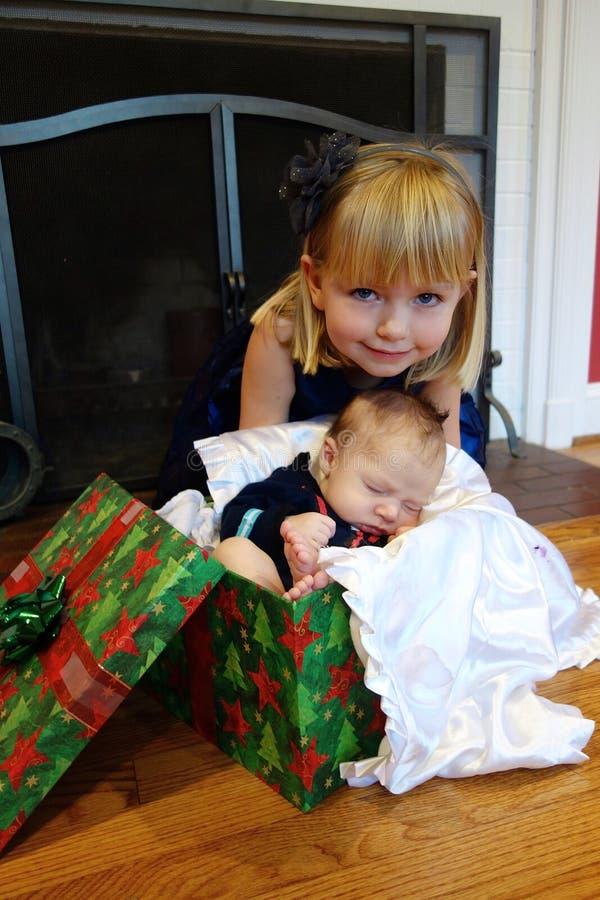 Irmã mais velha com o irmão novo do bebê no Natal fotografia de stock