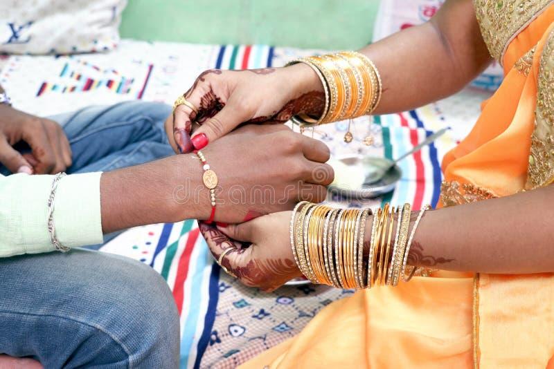 Irmã nova indiana que amarra o rakhi no pulso do irmão foto de stock royalty free