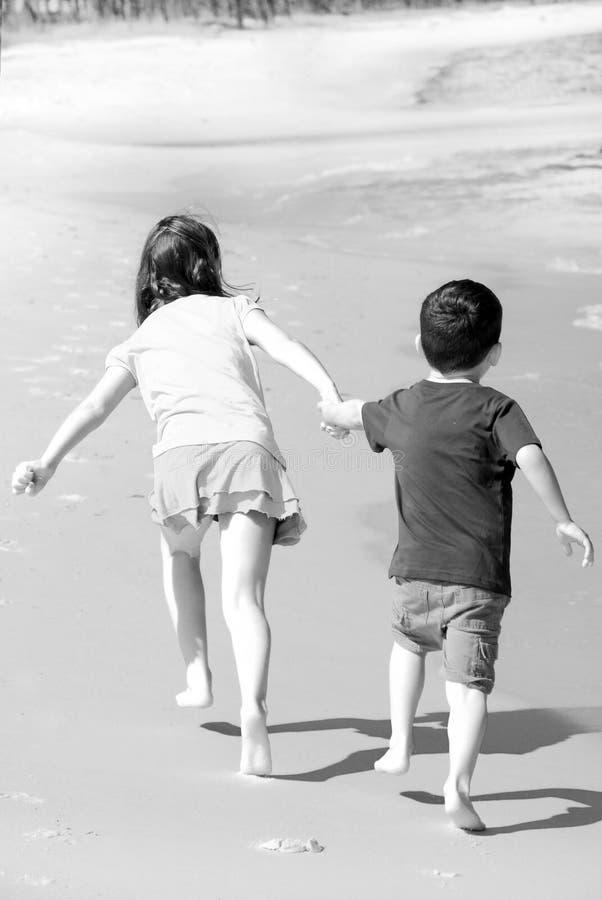 Irmã que puxa o irmão na praia foto de stock royalty free