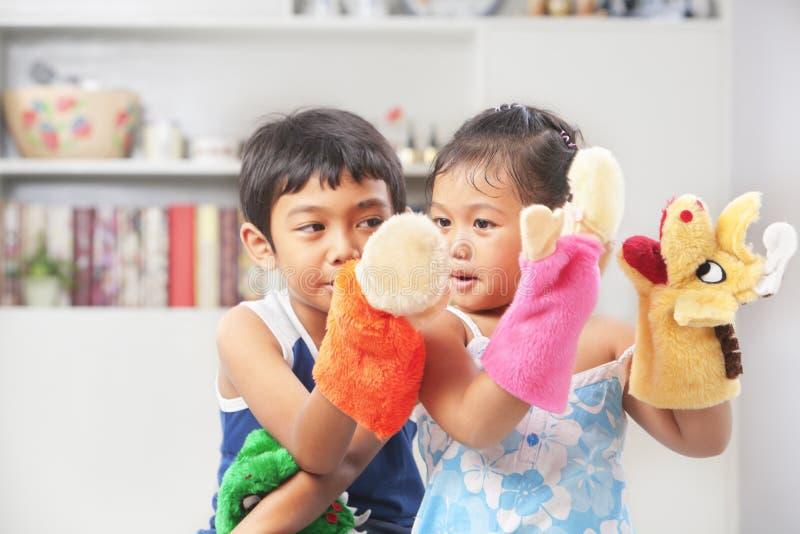 Irmão asiático que joga o fantoche de mão fotografia de stock