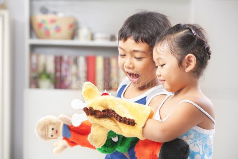 Irmão asiático que joga o fantoche de mão foto de stock royalty free