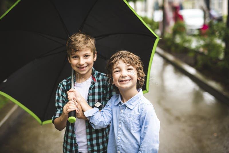 Irmão bonito de dois meninos, andando em um parque em um dia chuvoso fotos de stock royalty free