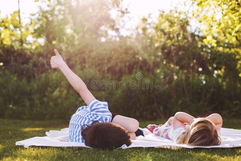 Irmão com sua parte traseira exterior da irmã mais nova duas crianças que encontram-se na grama foto de stock