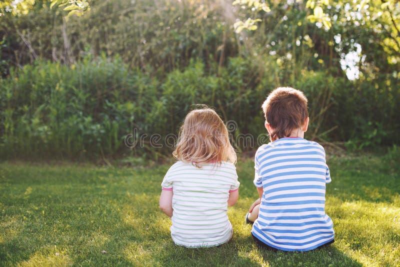 Irmão com sua parte traseira exterior da irmã mais nova duas crianças sentam-se na grama fotografia de stock royalty free
