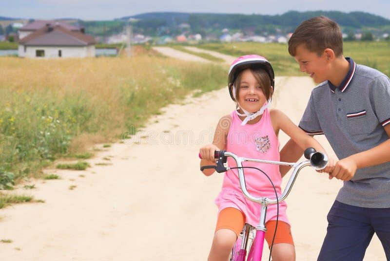 Irmão da juventude que ensina sua irmã mais nova montar uma bicicleta Menina em um capacete protetor cor-de-rosa em passeios cor- fotografia de stock royalty free