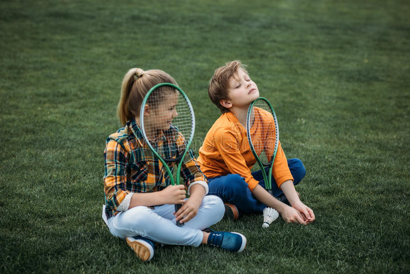 Irmão e irmã com as raquetes de badminton que sentam-se no campo verde fotografia de stock royalty free
