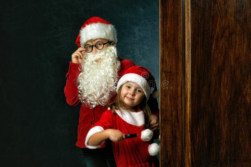 Irmão e irmã engraçados em trajes do Natal no fundo escuro fotos de stock