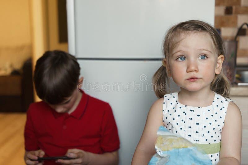 Irmão e irmã na cozinha que comem e que jogam no telefone fotografia de stock