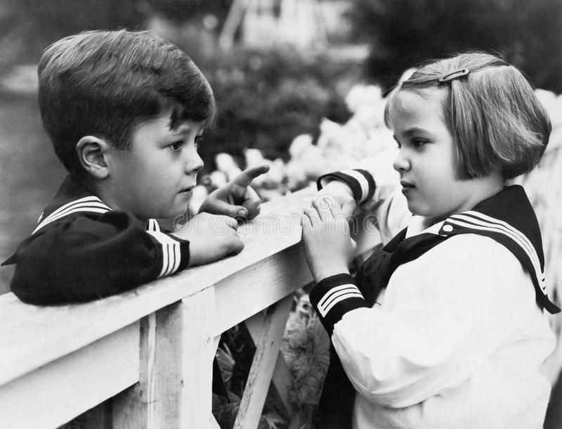 Irmão e irmã que falam um com o otro (todas as pessoas descritas não são umas vivas mais longo e nenhuma propriedade existe Garan fotografia de stock