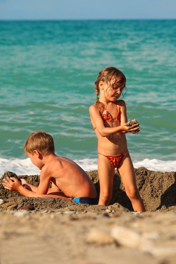 Irmão e irmã que jogam após a nadada na praia fotografia de stock
