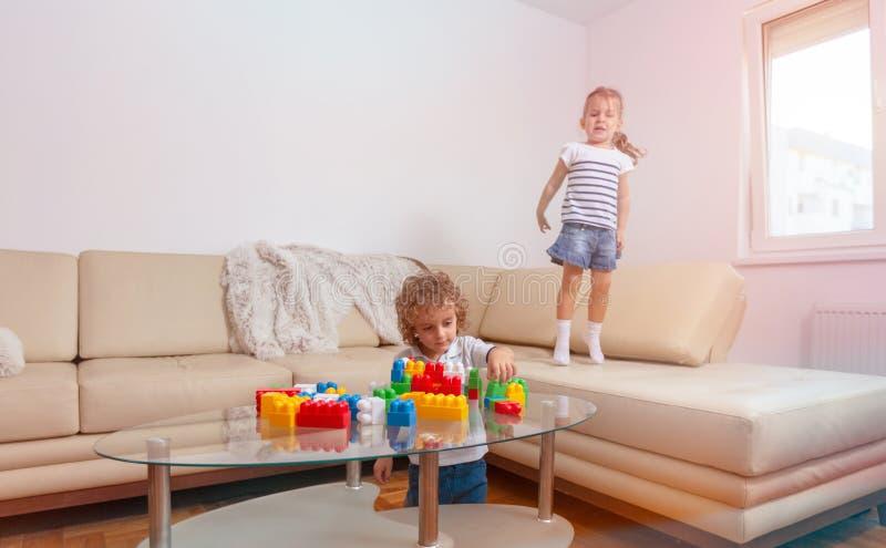 Irmão e irmã que jogam com brinquedos e que têm o divertimento junto imagens de stock