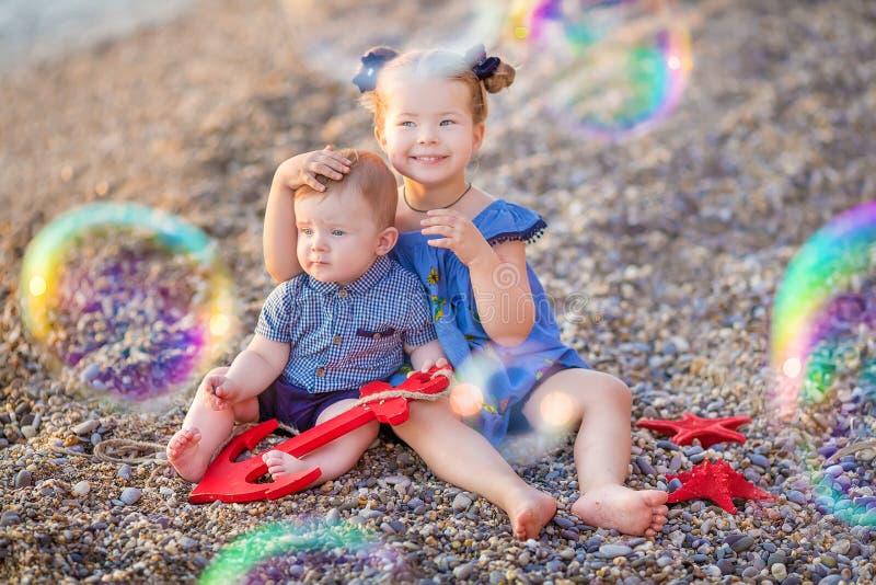 Irmão e irmã que jogam na ruptura da costa na praia durante o dia de férias quente do verão com bubles imagens de stock royalty free