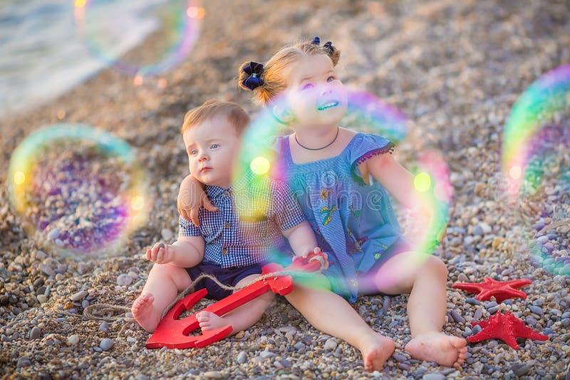 Irmão e irmã que jogam na ruptura da costa na praia durante o dia de férias quente do verão com bubles fotografia de stock