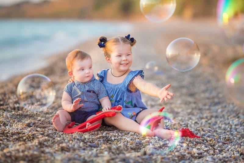 Irmão e irmã que jogam na ruptura da costa na praia durante o dia de férias quente do verão com bubles fotografia de stock royalty free