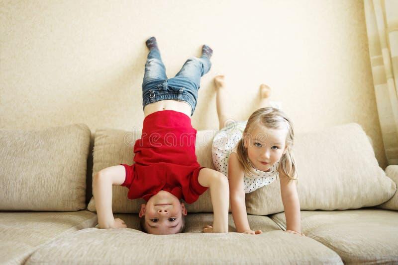Irmão e irmã que jogam no sofá: o menino está de cabeça para baixo fotos de stock royalty free