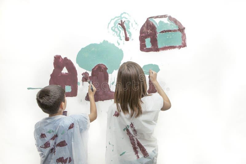 Irmão e irmã que pintam uma imagem imagens de stock royalty free