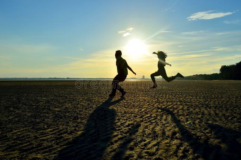 Irmão e irmã que saltam na praia fotografia de stock royalty free