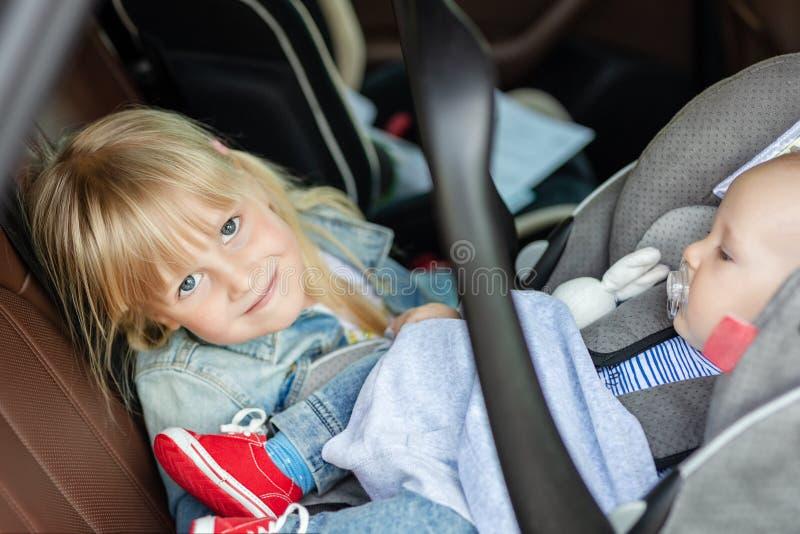 Irmão e irmã que sentam-se no carro no assento da segurança Irmãos nos lugares do passageiro que têm o divertimento junto durante fotografia de stock royalty free