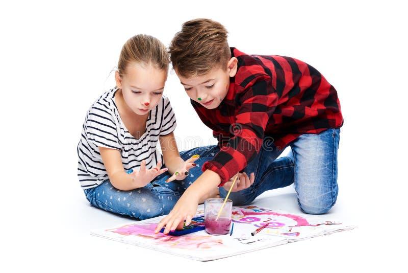 Irmão e irmã que têm o divertimento que pinta com aquarelas Crianças criativas felizes na classe de arte Conceito da terapia da a foto de stock