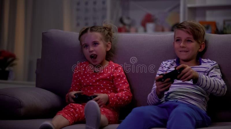 Irmão entusiasmado e irmã que jogam jogos de vídeo usando o manche na noite, divertimento fotografia de stock