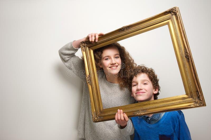 Irmão feliz e irmã que guardam a moldura para retrato imagem de stock royalty free