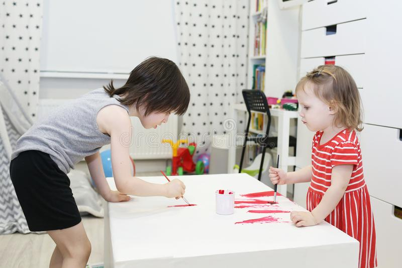 Irmão mais novo 5 anos e irmãs 2 anos que pintam em casa fotografia de stock
