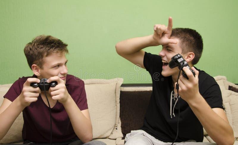 Irmão mais novo de arrelia do adolescente ao jogar jogos de vídeo imagens de stock royalty free
