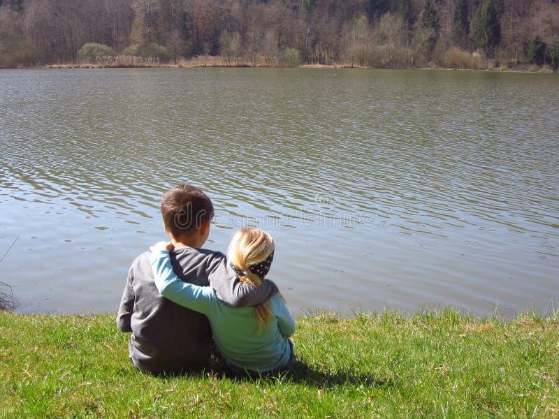 Irmão mais novo e irmã pelo lago fotografia de stock royalty free