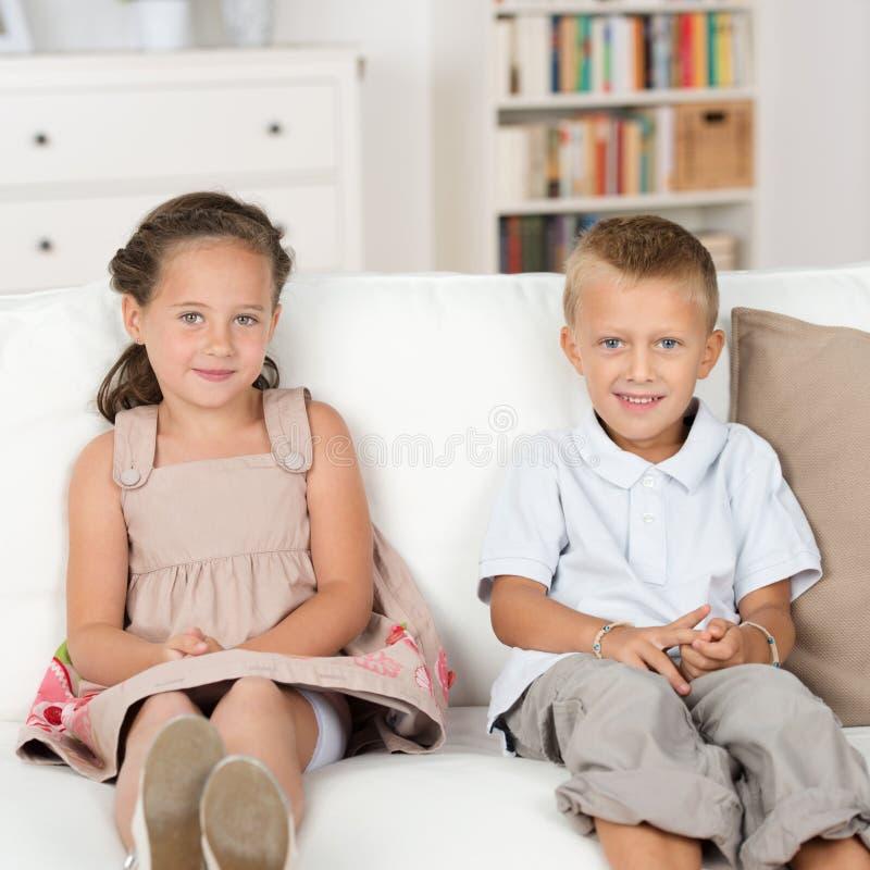 Irmão mais novo e irmã que sentam-se em um sofá fotos de stock