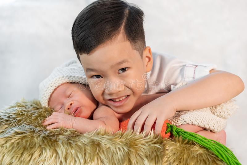 Irmão que abraça o bebê recém-nascido imagem de stock