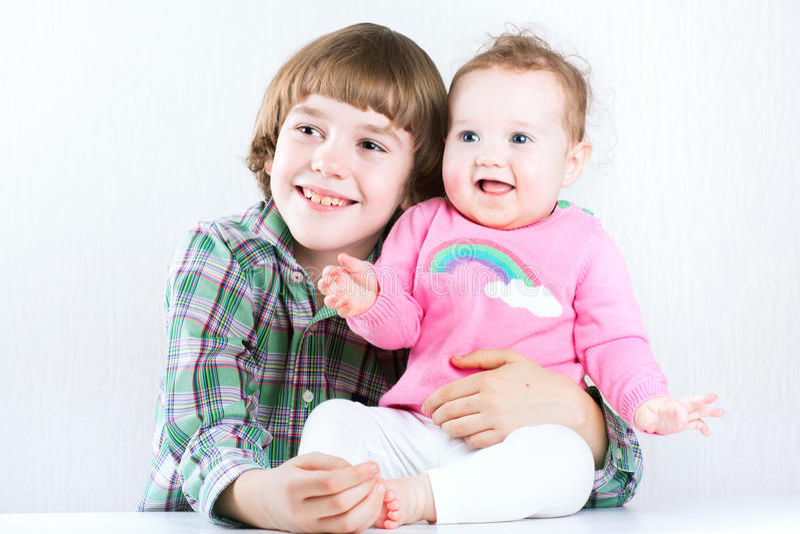 Irmão que abraça sua irmã do bebê, ambos que vestem camisas verdes e cor-de-rosa imagens de stock