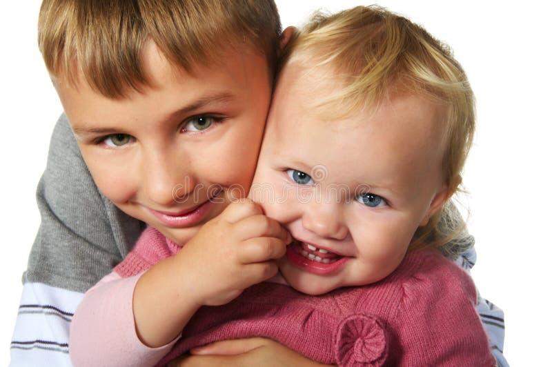 Irmão que abraça sua irmã pequena foto de stock royalty free