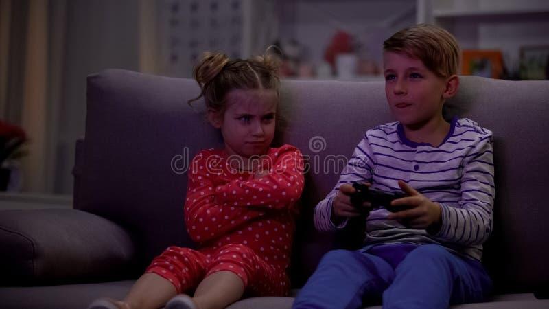 Irmão que joga o jogo de vídeo usando o manche, irmã que toma a ofensa para afrouxar imagens de stock royalty free