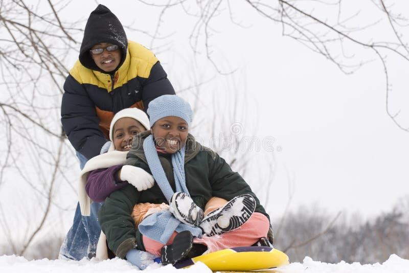 Irmãos afro-americanos e irmã que deslizam em um trenó fotos de stock