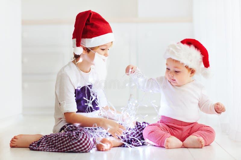 Irmãos bonitos do irmão, crianças em chapéus do ` s de Santa e festão que joga em casa imagem de stock