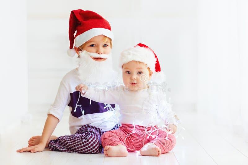 Irmãos bonitos do irmão, crianças em chapéus do ` s de Santa e festão que joga em casa fotografia de stock