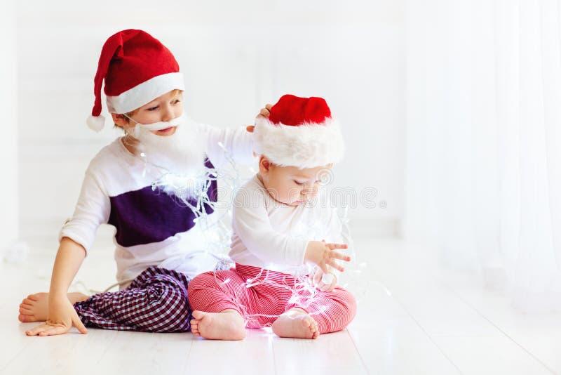 Irmãos bonitos do irmão, crianças em chapéus do ` s de Santa e festão que joga em casa foto de stock royalty free
