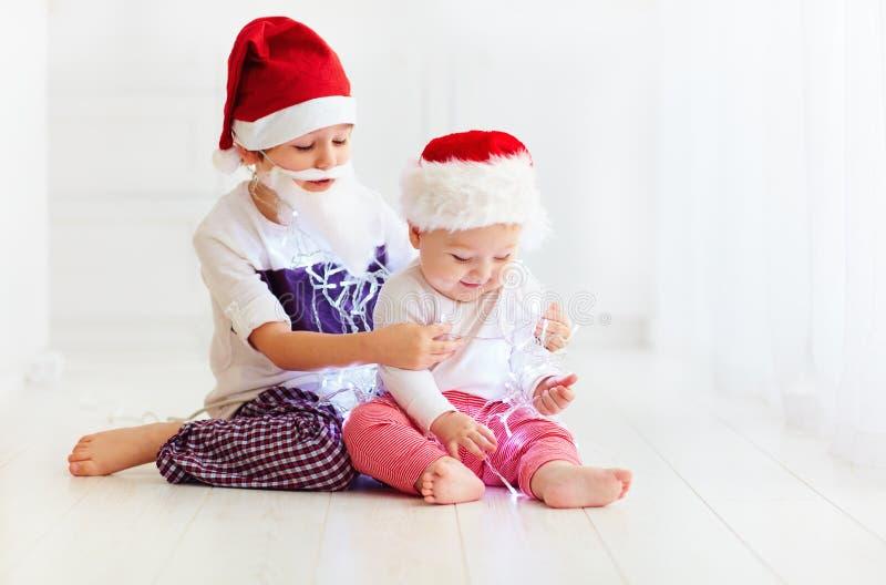 Irmãos bonitos do irmão, crianças em chapéus do ` s de Santa e festão que joga em casa fotografia de stock royalty free