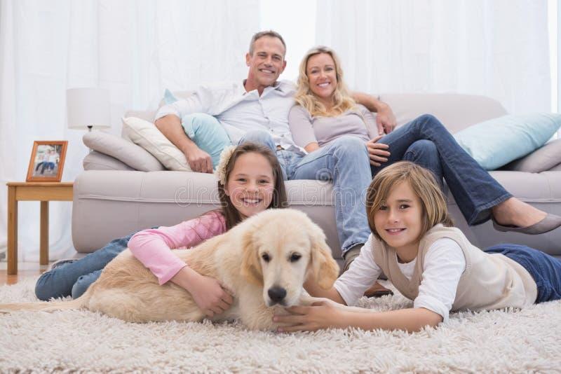 Irmãos bonitos que jogam com o cão com seu pai no sofá imagem de stock royalty free