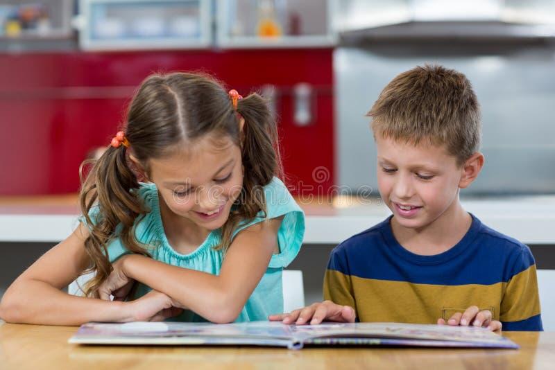 Irmãos de sorriso que olham o álbum de fotografias na cozinha fotos de stock royalty free