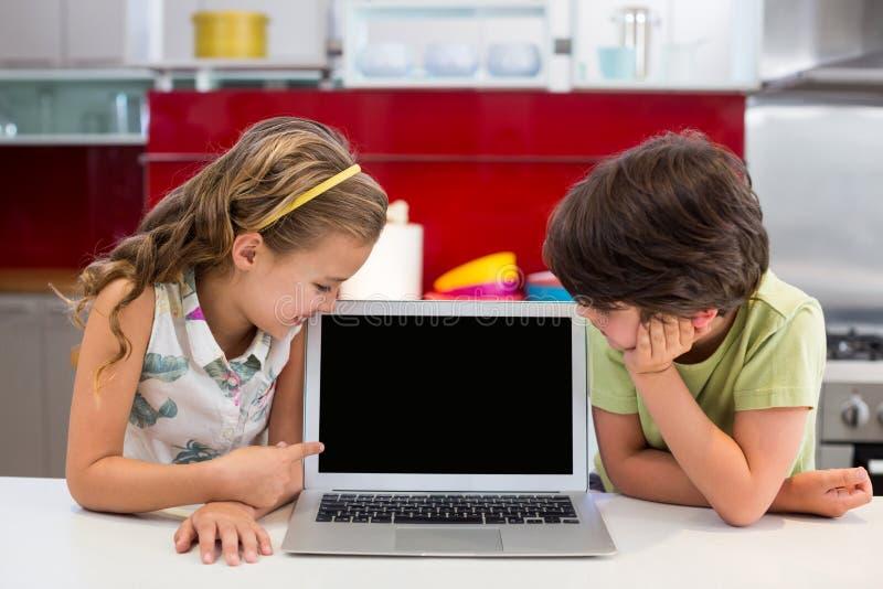 Irmãos de sorriso que olham o portátil imagem de stock royalty free