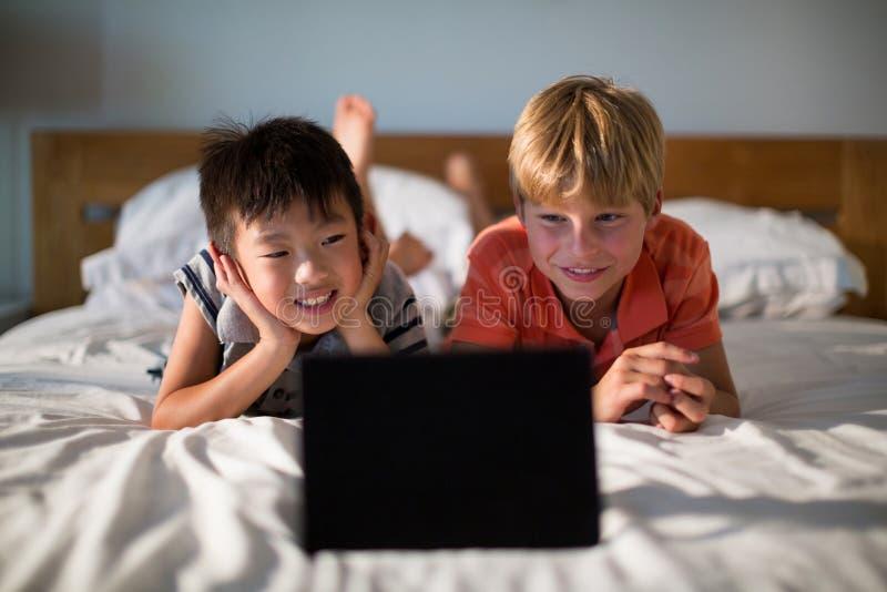 Irmãos de sorriso que olham a tabuleta digital na cama fotografia de stock royalty free
