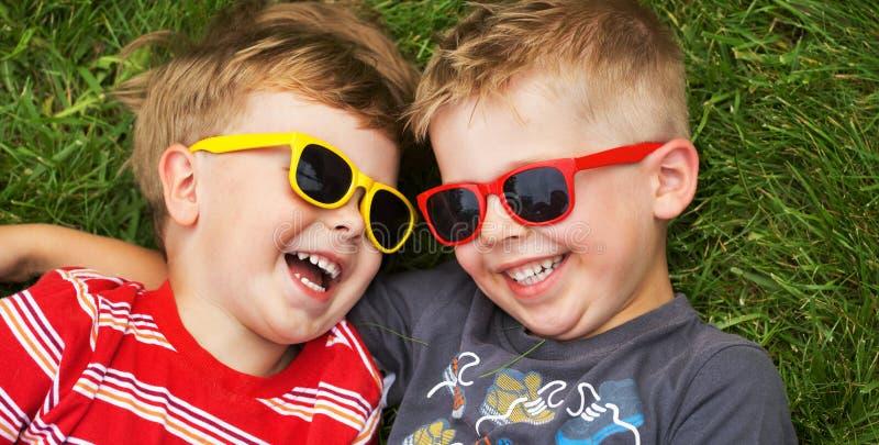 Irmãos de sorriso que vestem óculos de sol extravagantes fotografia de stock